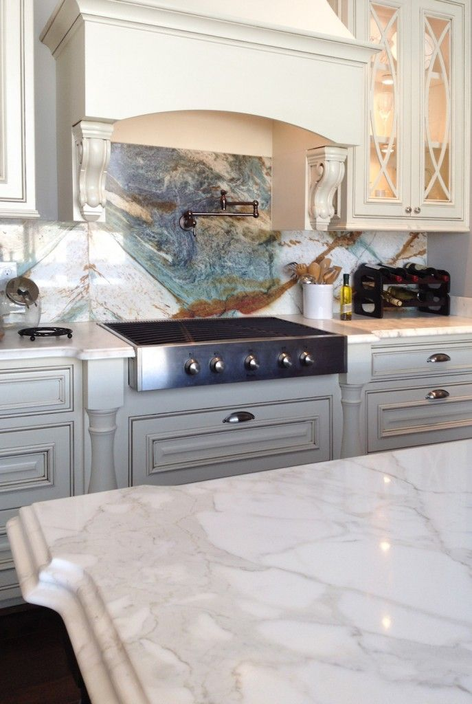 Beautiful kitchen with three different stone colors! Island: Calacatta Gold Polished marble. Perimeter: Mountain White Honed marble. Full Height Backsplash: Blue Louise quartzite.