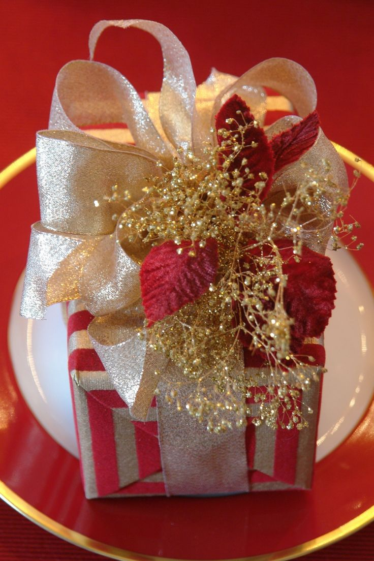 Design | Carolyne Roehm with red and silver striped gift wrap paper and a red ribbon and bow!!! Bebe'!!! Love the gold sprig trim and red velvet leaves!!!