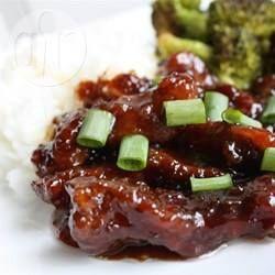 Rindfleisch mit Frühlingszwiebeln auf mongolische Art. Ein klassisches Gericht aus der Mongolei bei dem Rindfleisch in Stärkemehl gewälzt, kurz frittiert wird und dann in einer süßen aromatischen Sojasoße gekocht wird. Mit Reis oder Nudeln servieren. @ de.allrecipes.com