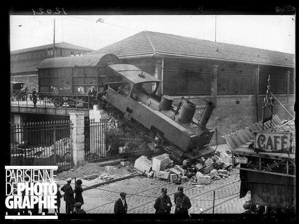 Guerre 1914-1918.  Une locomotive dans la rue  : le 19 mai 1917 au matin,  une locomotive servant à amener les wagons sur la voie ferrée de l'entrepôt de la Halle aux Vins, est tombée, par suite d'une fausse manoeuvre, dans la rue de Jussieu, après avoir démoli le butoir . Photographie parue dans le journal  Excelsior  du dimanche 20 mai 1917.
