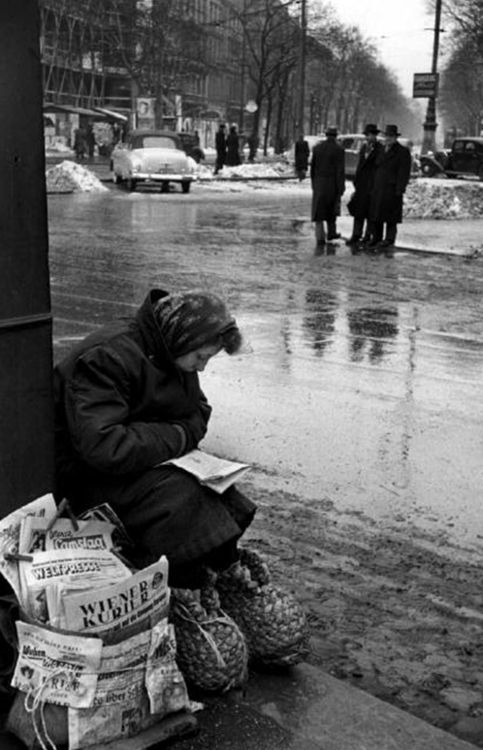 Erich Lessing  Vienna. Schottentor. Newspaper vendor keeping her feet warm in straw shoes. 1953