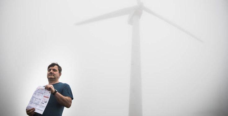 José Manuel Felpeto, en un parque eólico de Muras, sostiene una factura de luz con descuento.