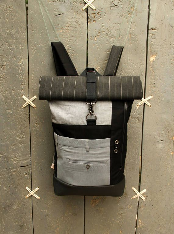 Black and grey roll top upcycled rucksack using part from a gray men's trousers to create a double pocket on the front, by 'eating the goober'