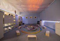Foto Raum der Stille, bunt ausgeleuchtet mit Hockern und einem aus bunten Tüchern gelegten Mittelkreis