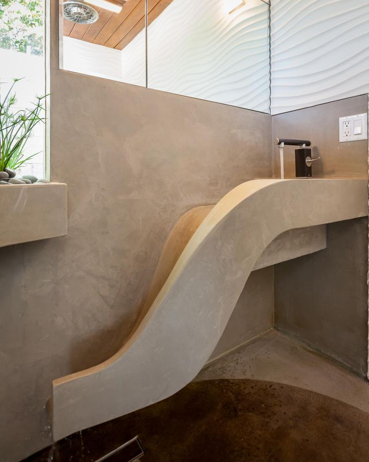Photographic Gallery Contemporary Bathroom With Sculptural Sink The focal point of this neutral bathroom is a sculptural sink that allows water to trickle down a slide like