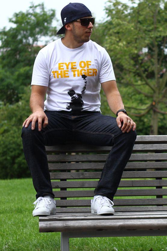 T-shirt Eye of the Tiger Dit rechte model T-shirt voor mannen is gemaakt van voorgekrompen ringgesponnen katoen en heeft een opdruk van Rocky Balboa's Eye of the Tiger. De hoge kwaliteit en goede verwerking zijn zichtbaar in de dubbele naden aan de mouwen en de zoom en de tweevoudig gelegde kraag in 1X1 ripp.