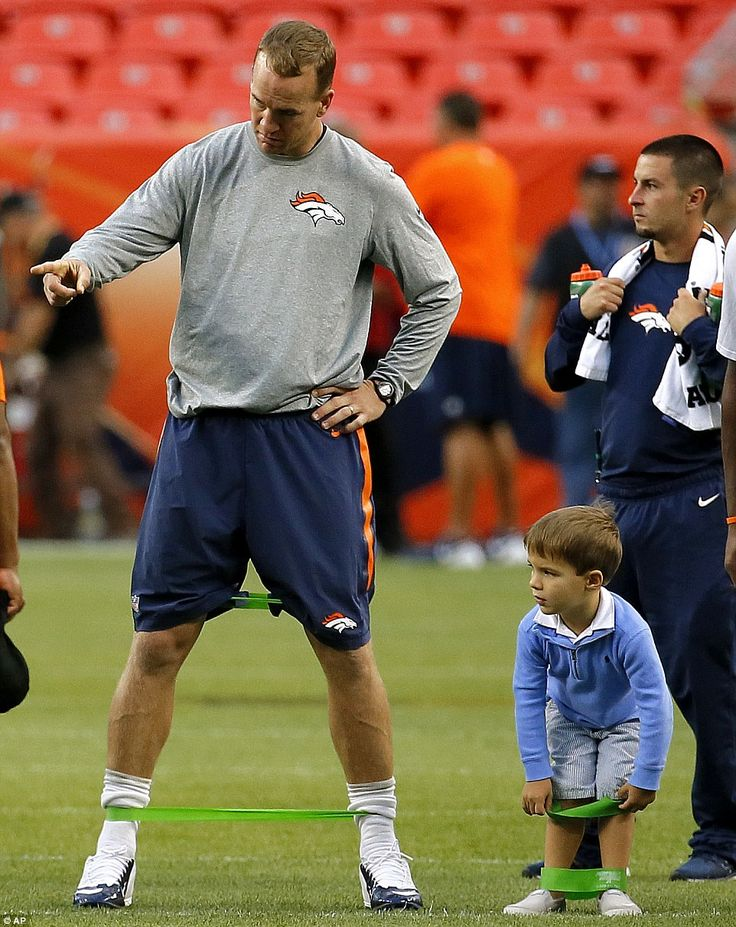 Learning from the master: Manning gave some instruction to his son before the Broncos 22-20 loss to the Arizona Cardinals in Denver