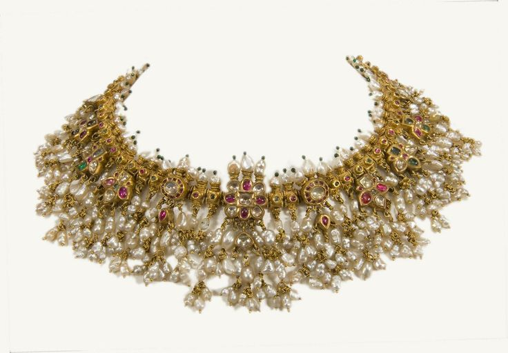 A gold necklace, Guttapusal. India, Andra Pradesh, 19th century. Provenance: A gold necklace, Guttapusal, set with rubies, emeralds and white sapphires. The whole is decorated with suspended pearls of exceptional size and quality. Bunches of small pearls, Gutta, pierced as beads, Pusal. The name of this ornament originated in areas close to the ancient pearl fisheries along the Coromandel coast