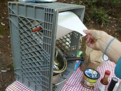 8 Things You Need For Camping That You Might Forget : such as this diy paper towel holder made out a plastic crate with a rod through the middle... keeps paper towels from blowing away or falling on the ground!