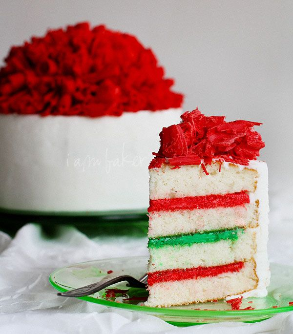 Chocolate Curls Christmas Cake. Picture only. No recipe. White cake with red and green colored frosting. Frosted white and topped with red  colored chocoloate curls...Pretty!