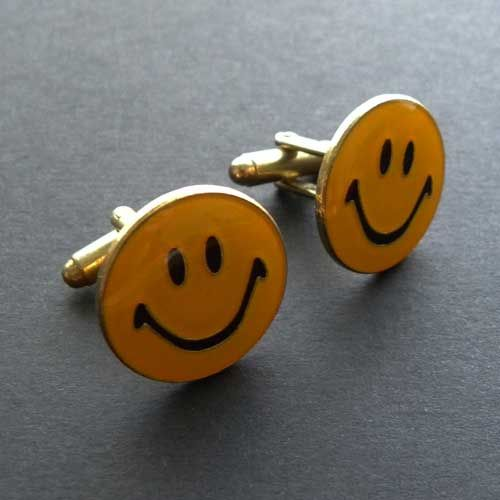 Modern pair of novelty mens cufflinks with a bright and cheerful yellow Smiley Face design Each has a black pair of eyes and a big wide smile