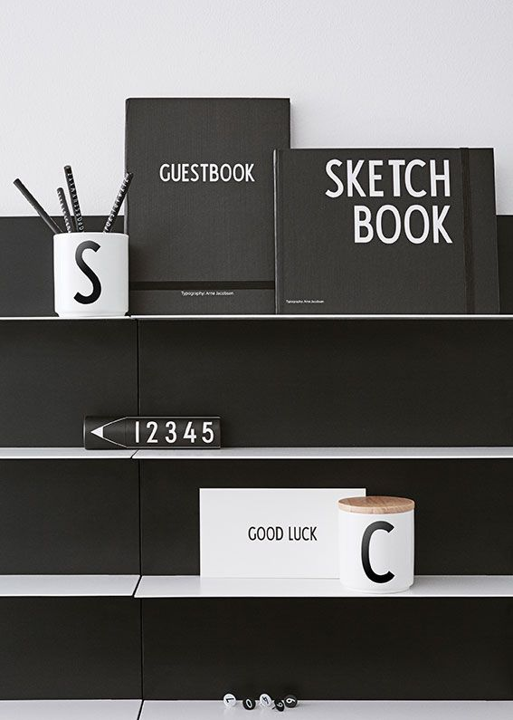 A range of stationery on Paper Shelves. Create a graphic home office design with black and white furniture, notebooks, writing utensils and decoration items.
