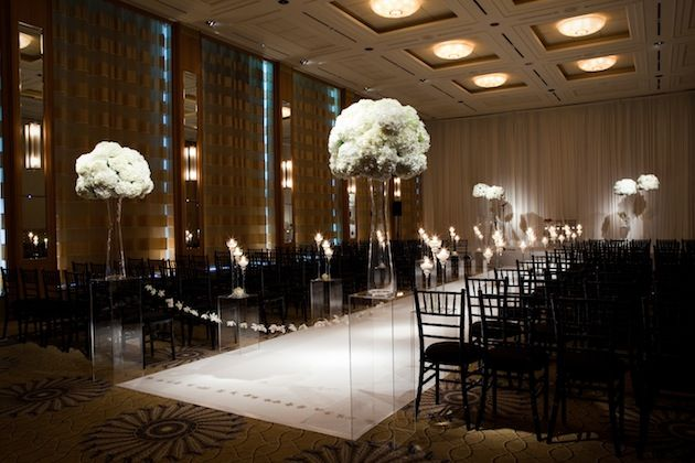 Simple Black and White indoor ceremony decor  Like the Flores on stands (Crystal across aisleway)