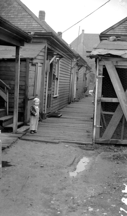 Slum dweller, 300 block East Cordova, 1943  Photograph shows a small child standing by a row of houses in the slum district of Vancouver. Source: Photo by Jack Lindsay, City of Vancouver Archives #1184-638