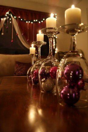 Wijnglazen omgedraaid, kerstballen in het glas en een kaars erop