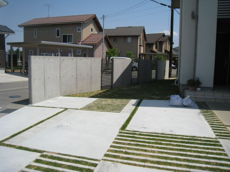 大胆に植物のスリットを使った、土間コンクリートのアプローチ。