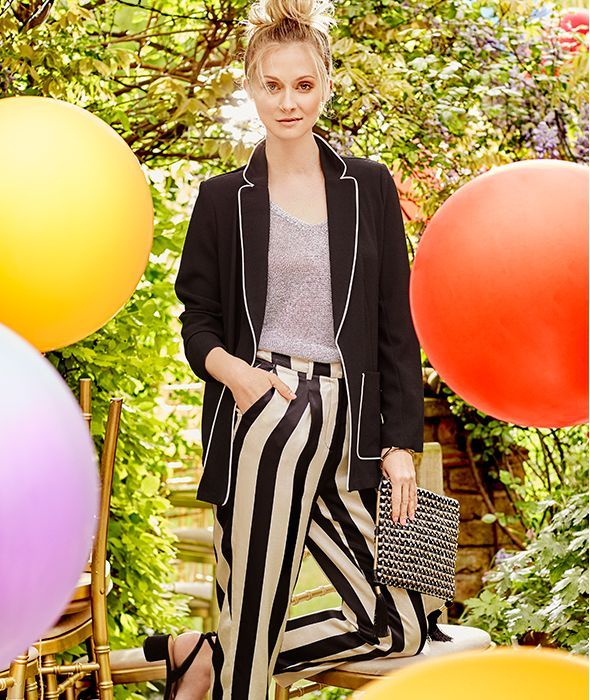 Woman wears black striped trousers with silver cami top, black blazer and printed clutch