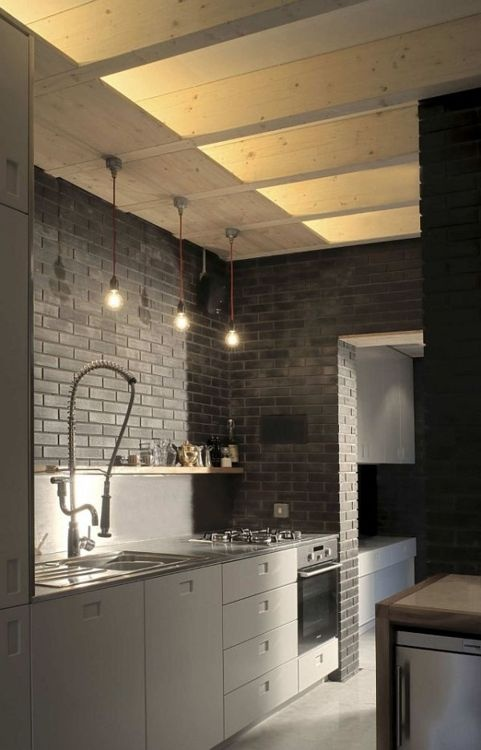 Black / grey kitchen space. Notice the bricks.