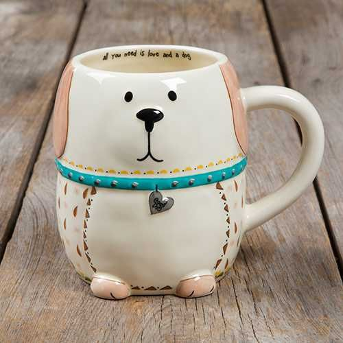 """Dog Folk Art Mug - This folk art mug will have you smiling every time you drink from it! It features an adorable dog design and the sweet sentiment, """"All you need is love and a dog"""" on the inside! This hand sculpted, ceramic mugs is microwave and dishwasher safe."""