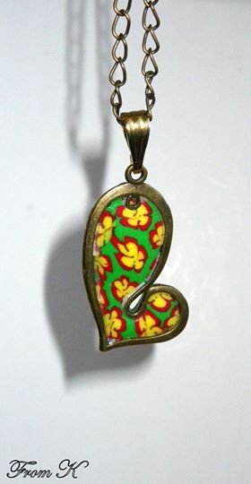 """Heart Charm Necklace. Handmade, using slices of polymer clay Cane, hand-shaped into a """"flower"""" pattern. It is then attached to a metal copper heart, sanded and buffed for a smooth finish. Aprox 3x2 cm big Chain is about 60 cm long 15.00 Ron"""