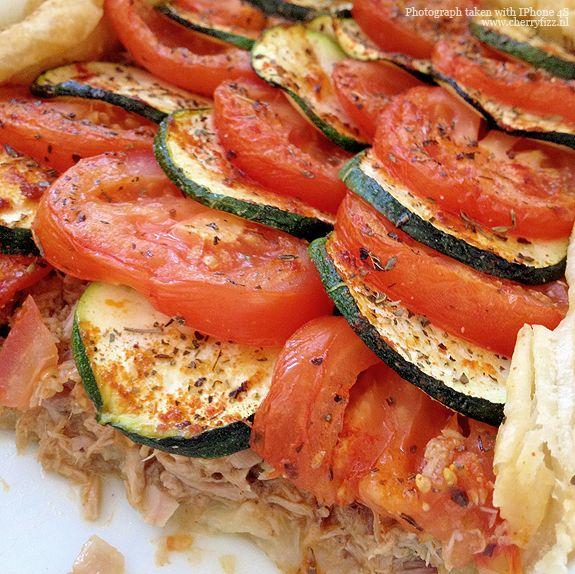 HARTIGE TAART TONIJN, TOMAAT EN COURGETTE Bladerdeeg, 2 blikjes tonijn, courgette, ui, tomaat, olijfolie, Italiaanse kruiden. Oven voorverwarmen 220 graden. Olie in een pan en uitjes, tonijn en kruiden in bakken. Zet opzij. Ovenschaal invetten en strooi er beetje bloem in. Leg er bladerdeeg in en prik met een vork een aantal gaatjes, doe dan tomaat en courgette in de taart. Daaroverheen nog een beetje olijfolie, peper, zout, Italiaanse kruiden en knoflook. Ca. 30 min. in de oven.