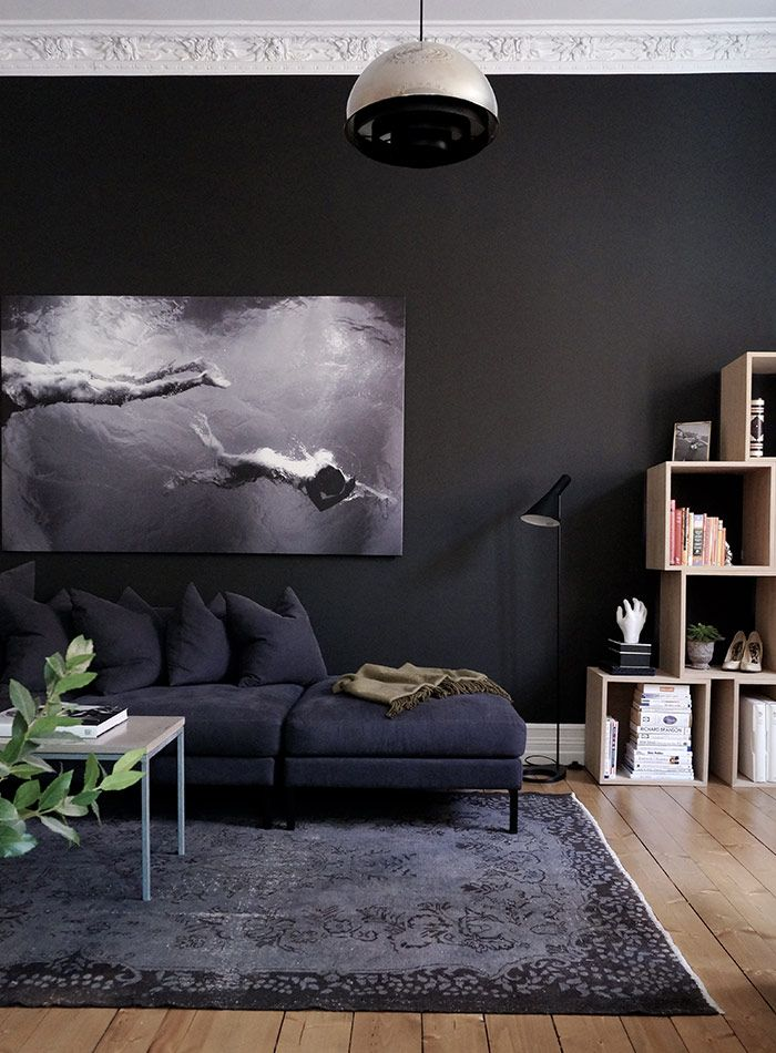 Moody tones of charcoal are layered together for a sophisticated look in this living room. The sofa blends into the wall for a dark and cozy feel. Photographer: Pia Martine Gautier Bjerke