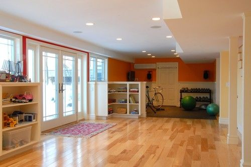 In this playroom–home gym, built-in toy storage and exercise equipment are stacked against the walls, which leaves plenty of space in the middle for kids to play or for anyone to exercise. The built-in bookcase helps separate one side from the other.