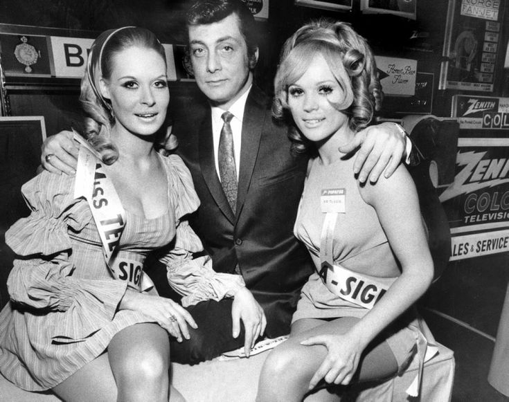 Penthouse magazine publisher Bob Guccione poses with two Penthouse Pets at the New York Hilton in 1968.