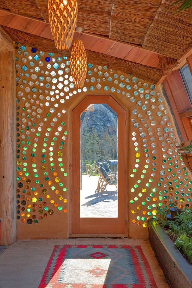 EarthShip home with recycled glass bottle mosaics <3