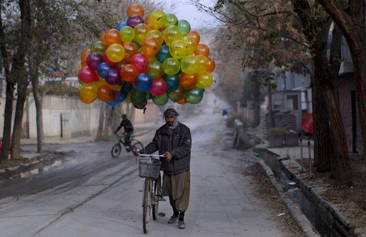 A vendor pushes his balloon-laden bike through Kabul looking for customers on the Eid al-Adha religious holiday Photograph: Muhammed Muheisen/AP (via Eyewitness: Kabul balloon seller | World news | The Guardian)