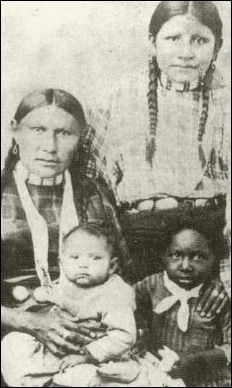 Cherokee mother and children. Note the African American child with them. That was a common thing then.