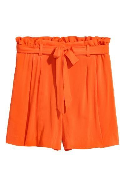 Short court tissé. Modèle taille haute avec ceinture à nouer et plis couchés en haut. Braguette zippée avec agrafe. Poches latérales.