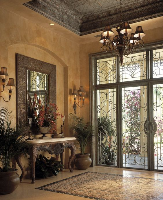 Mediterranean Entryway with Uttermost harvest serenity mirror, Chandelier, simple marble tile floors, Wall sconce