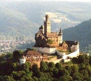 Touring Castillos en Europa. Crucero por el río Rin. El tesoro más grande del río Rin es el castillo de Marksburg. Construido en el siglo XIII, el castillo de Marksburg se encuentra tan cerca del precipicio que en algunas secciones sus paredes se desvanecen en las piedras de la montaña y se confunden entre sí. Las escaleras y la entrada principal donde tallado directamente en la pizarra de la roca. El techo puntiagudo también está hecho de pizarra, que fue recuperado de la base del castillo