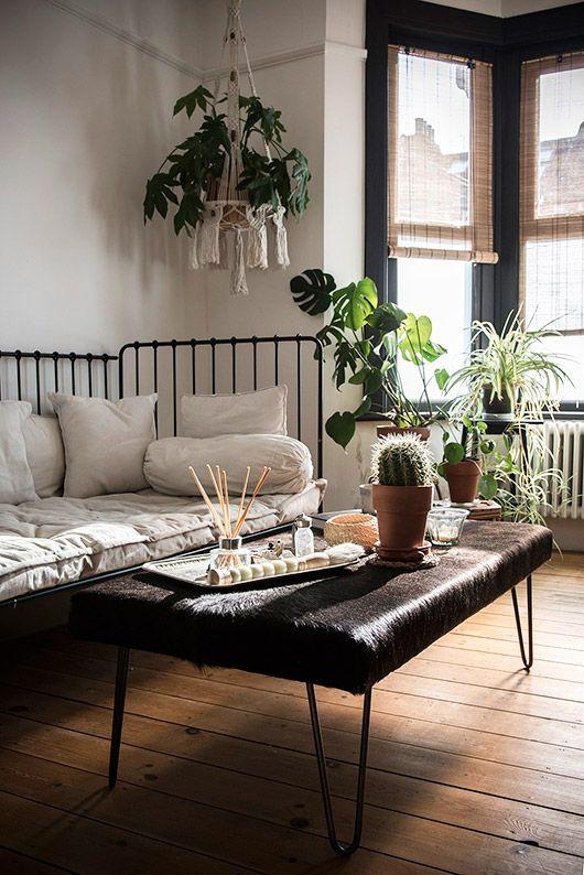 Salon au style bohème, lit en fer forgé transformé en canapé et plantes d'intérieur