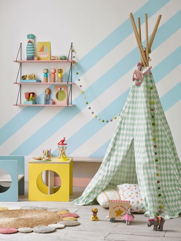 Décoration de chambre d'enfant : parquet clair, mur rayé blanc et bleu ciel, tipi d'indien motif harlequin vert pastel, étagères roses pastel, combiné bureau et chaise bleu et jaune, tapis rond, guirlande petits pompons couleurs pastel