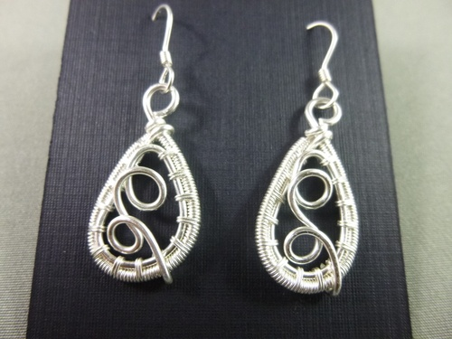 Non-tarnish silver wire frame, wrapped, embellished, coiled and finished with sterling silver earwires.
