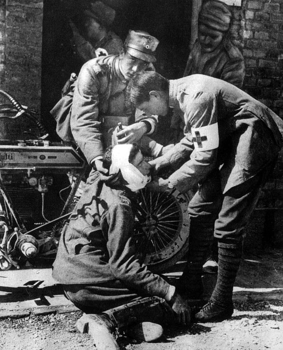 World War I, Italian dispatch motorcycle rider receiving first aid, 1915