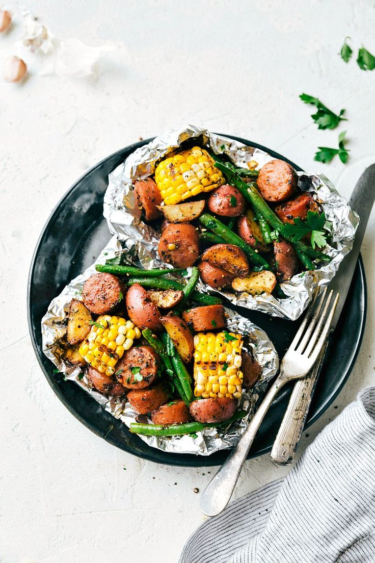Easy Tin Foil Pack Garlic Butter Sausage and Veggies. A delicious meal that takes 15 minutes prep time or less! chelseasmessyapron.com