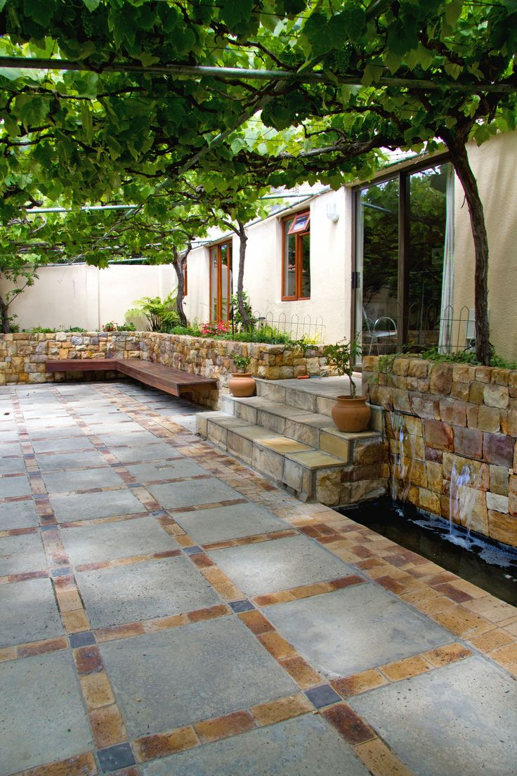 Complete courtyard upgrade. Sandstone mason water feature and walls created, floor materials recycled. Floating decking bench and soft greenery.