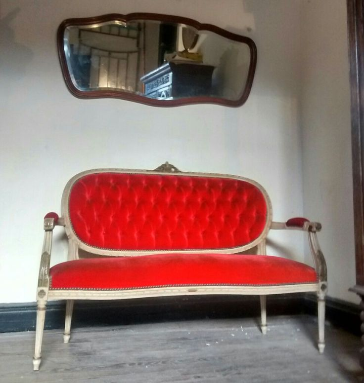 Sillón Luis XVI tapizado en pana roja con capitone. Espejo biselado estilo francés