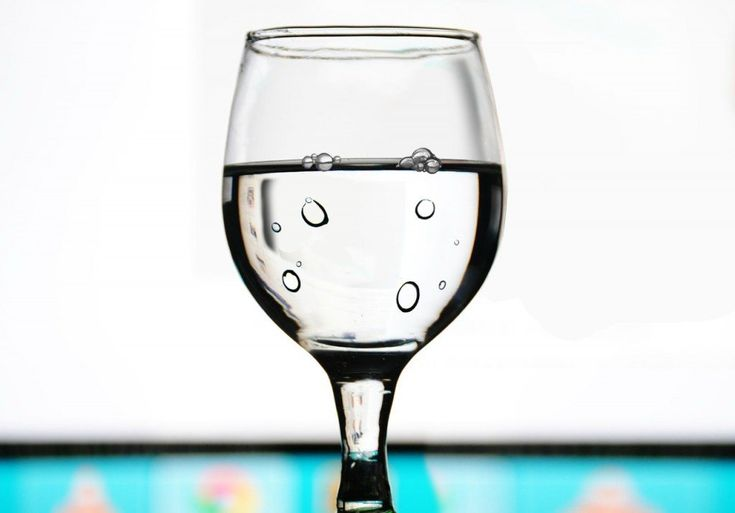 Fill a glass with water (at or below room temperature) and leave it undisturbed for a few hours (you can do this using tap water). You will eventually notice that very small bubbles begin to appear along the side