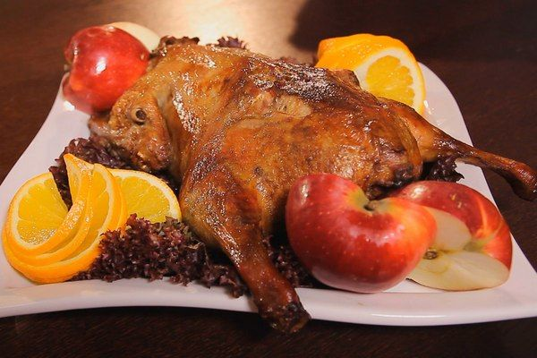 Roast duck with oranges and apples at home —