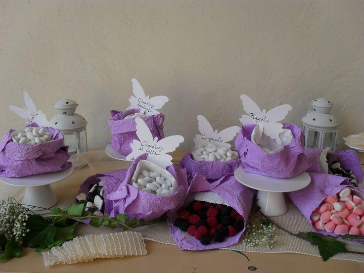 Un piccolo candybar dal sapore provenzale con alzatine in ceramica bianca e sacchetti di carta bianchi e lilla su cui si posano delicate farfalle segnagusto