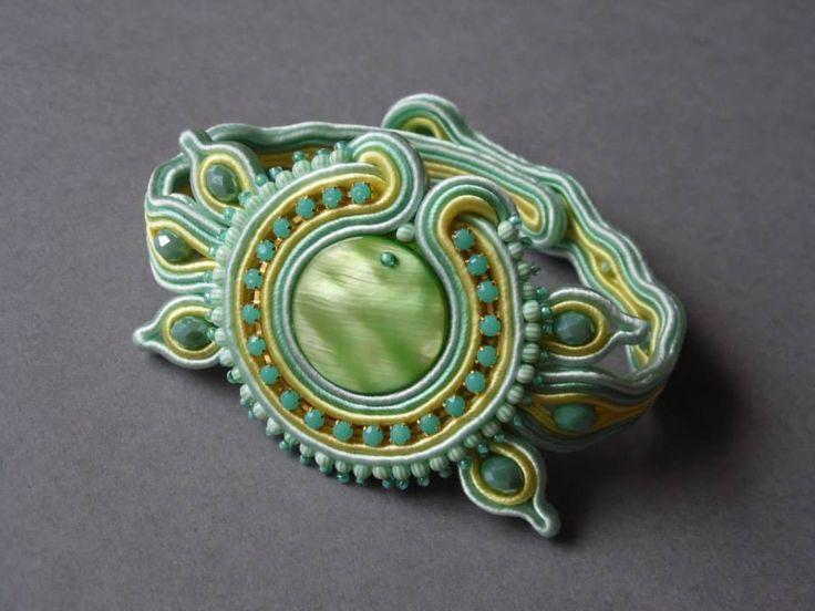 Bransoletka wykonana w technice haftu sutaszowego.W centrum znajduje się masa perłowa,otoczona taśmą cyrkoniową i szklanymi koralikami.Zapięcie na 2 koraliki.Częściowo wykończona filcem.