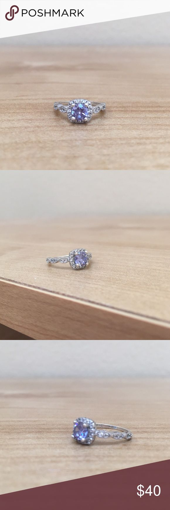 Art Deco Accent Halo Promise Ring  Silver with rhodium plating. Center stone is approximate equivalent of .75 carat diamond. Synthetic Tanzanite and diamond simulants in the halo. Art deco band. Gorgeous lavender/blue stone. Originally purchased from TigerGems on Etsy. Perfect as a promise ring for a lady or a special gift for yourself! As with all silver jewelry, this ring should be cleaned every so often. Not from Zales; listed for exposure. Zales Jewelry Rings