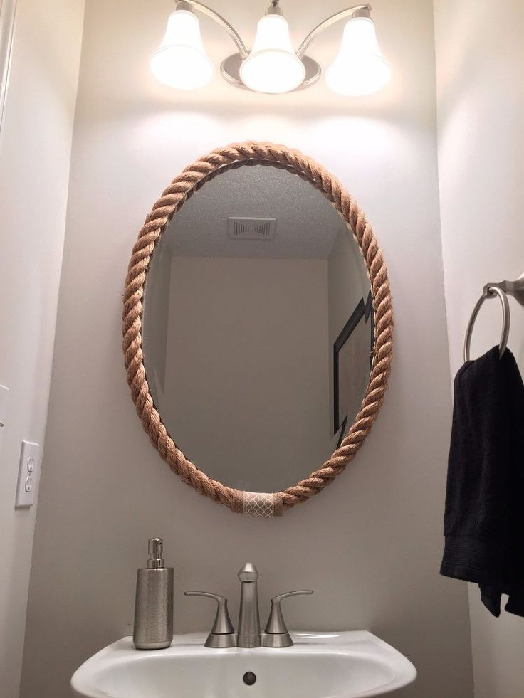 My powder room had a boring oval mirror that was glued onto the wall.  Since I couldn't replace it (easily), I decided to frame it with some rope to add texture…