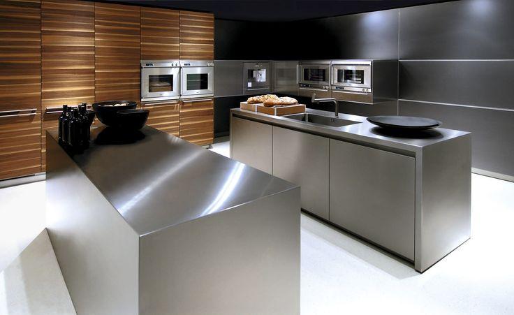 elegancka kuchnia ze sprzętami AGD umieszczonymi w kubikach zawieszonych przy panelach naściennych; efektowne wyspy kuchenne ze stali nierdzewnej i przykuwający uwagę fornir na zabudowie wysokiej