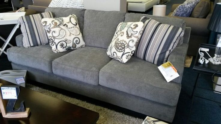 Lounge suite in muted grey. Scatter cushions in turquoise or blue to accent theme.