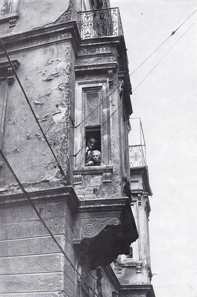 Beyoğlu'na eski bir binanin penceresinden bakan bir yaşlı kadın ve bir adam #istanbul #istanlook #birzamanlar